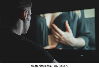 Un homme regarde un film érotique tard dans la nuit.