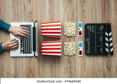 Man watching a film streaming online with popcorn, 3D glasses and clapboard, cinema and entertainment concept, flat lay
