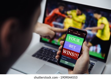 Man watching football online broadcast on his laptop and celebrate victory in betting at bookmaker's website. Betting and gambling concept