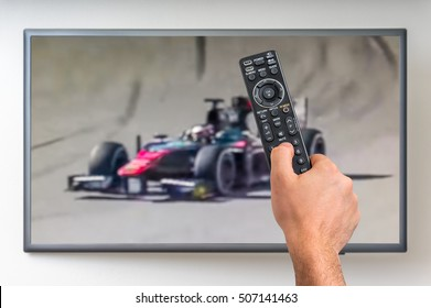 Man is watching formula one racing on TV and holding tv remote controller in hand