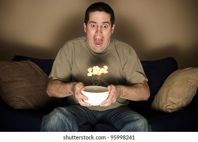 Man watching a horror movie jumps in shock