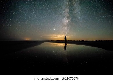 Man watching the milky way with falling stars and meteors on the Black Sea shore, Danube Delta, Romania.