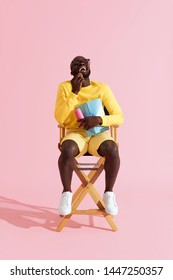 Man watching movie in cinema glasses laughing eating popcorn. Happy black male model in 3d glasses and yellow clothes sitting on director chair watching show on pink background
