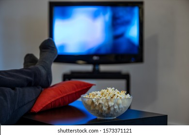 man watching a movie with foot over the table with popcorn