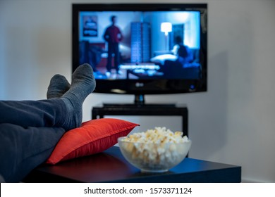 man watching a movie with foot over the table and bowl of popcorn