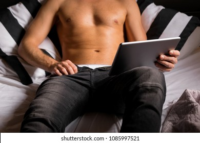 Man watching movie on tablet in bed