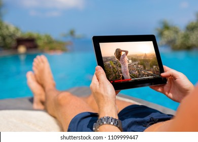 Man watching movie on tablet by the pool.