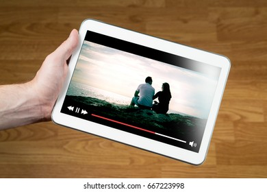 Man watching movie online with mobile device. Hand holding tablet with imaginary video player and film streaming service.