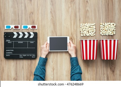 Man watching movies streaming online using a digital tablet, popcorn, 3D glasses and clapboard, cinema and entertainment concept