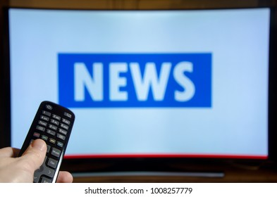 Man watching News on TV and using remote controller.