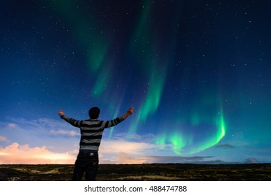 Man watching northern light over Iceland horizon. Traveler enjoying the experience of a life time. Aurora. Dream comes true. Tourist.