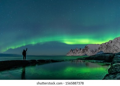 Man watching the northern lights, Aurora Borealis, Devil Teeth mountains in the background and a rock formation and the ocean in the foreground, Tungeneset, Senja Island, Troms, Norway, Europe