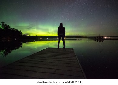 Man watching the northern lights, Muskoka, Ontario, Canada.