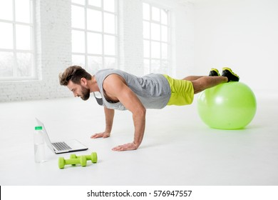 Man watching online trainig with laptop training on the fitball in the gym