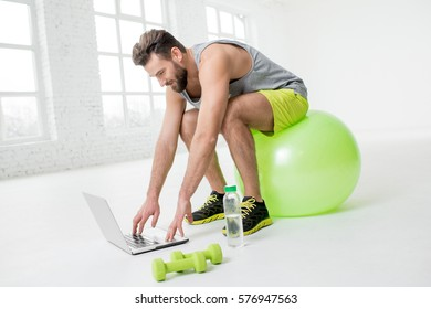 Man watching online trainig with laptop sitting on the fitball in the gym