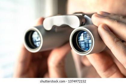 Man watching out the window with binoculars. Curious and nosy neighbour. Private detective or undercover cop investigating or spying. Curious person or stalker.