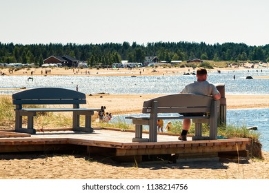 Man watching the people at the beach on a warm summer day at Kalajoki, Finland. The beach is very popular on warm days like this.