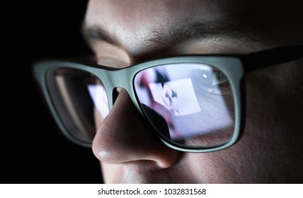 Man watching photo of young woman in bikini on social media. Erotic message sent by girlfriend. Reflection of laptop or smartphone screen on glasses.