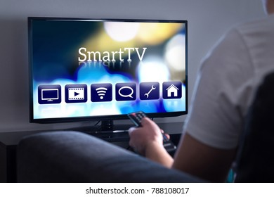 Man watching smart tv. Choosing movie or series from the menu. Person holding remote control. User interface on television screen.