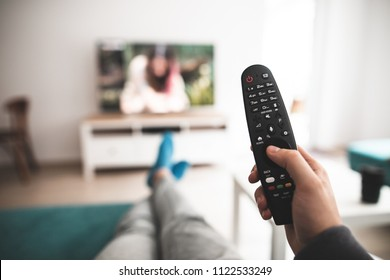 Man watching smart tv controlled by smart remote - point of view perspective