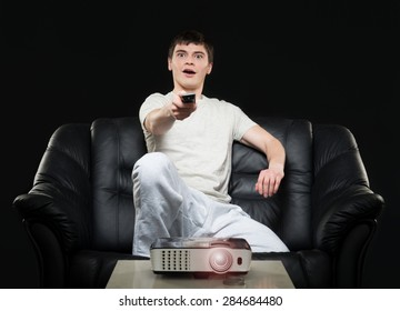 Man watching sport broadcast sitting on sofa at home.