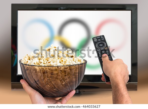 Man is watching sports games on TV and holds remote controller and popcorn in hands