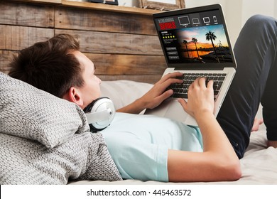 Man watching streaming series in a laptop computer, lying in the bed at home.