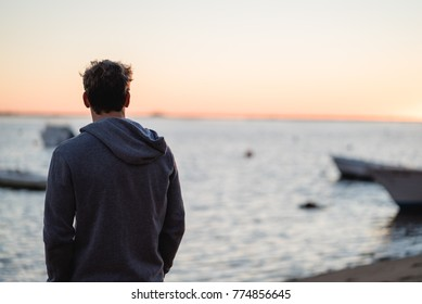 Man watching the sunrise from a beach in Portugal