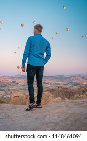 man watching sunrise, Goreme Capadocia kapadoya Turkey, Sunrise over the hills with hot air balloons in the sky , colorful landscape