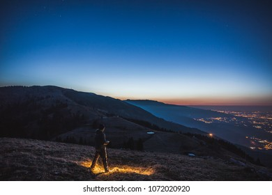Man watching the sunrise on the Veneto plain, Pian de le Femene, Veneto, Italy