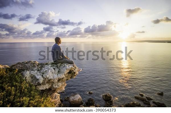 Mann beobachtet Sonnenaufgang, der auf Felsen neben dem Kliff sitzt. Malta, Europa