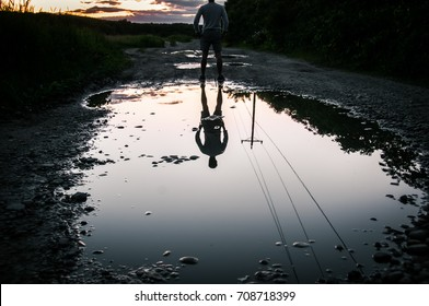 man watching sunset in front of reflective puddle