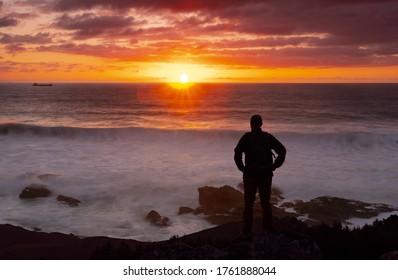 Hombre viendo la puesta de sol sobre el mar.