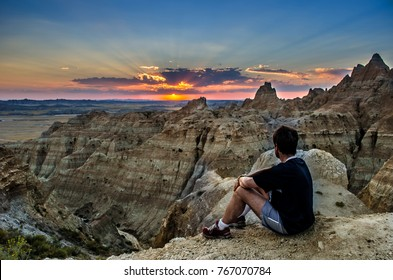 MAN WATCHING SUNSET OVER South Dakota BADLANDS