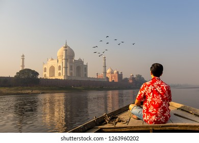 Man watching sunset over Taj Mahal from a wooden boat with bird flying over