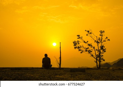 man watching the sunset in solitude