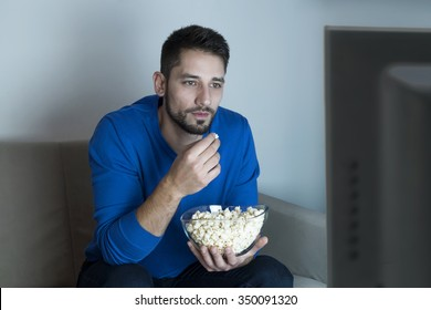 Man watching television and eating popcorn
