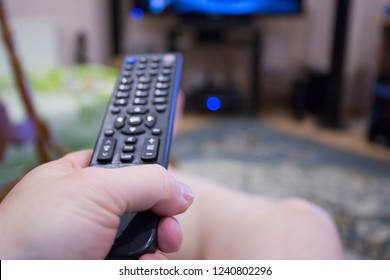 Man watching television . In hand control panel.