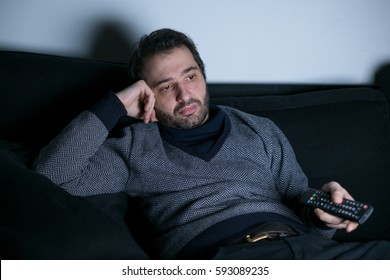 Man watching television at night lying on the couch