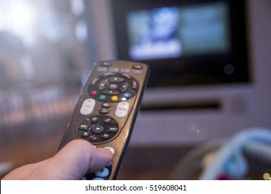 Man watching television using TV remote
