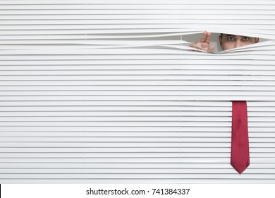Man Watching through window blinds