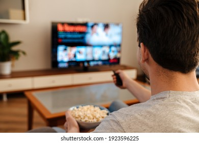 Man watching tv and eating popcorn at home on a couch, back view