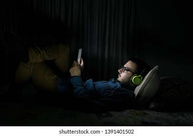 Man watching tv series in a tablet sitting on a bed in the night at home. Series, entertainment.