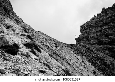 man watching the void from  a mountain cliff