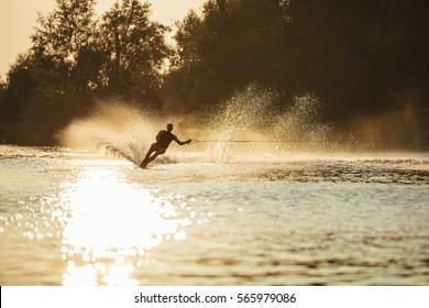 Man water skiing at sunset. Man riding wakeboard on lake water.