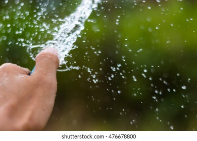 Man watering the garden from hose.