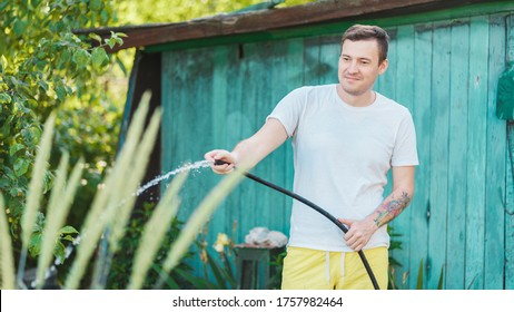 Man watering the garden from hose. Male spraying water on vegetables with a garden hose. A happy man with a hose takes care of the garden. Concept: gardening and garden care
