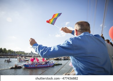 Man waving a rainbow flag during the annual event Gay Pride Parade, Euro Pride 2016, August 6