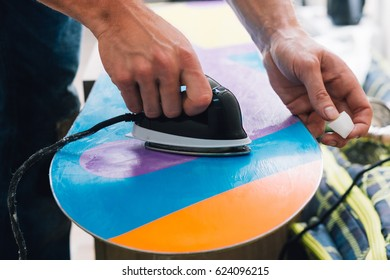 man is waxing a colorful snowboard with hot iron and wax