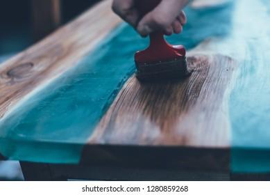 man waxing epoxy table. Custom furniture. Modern interior
